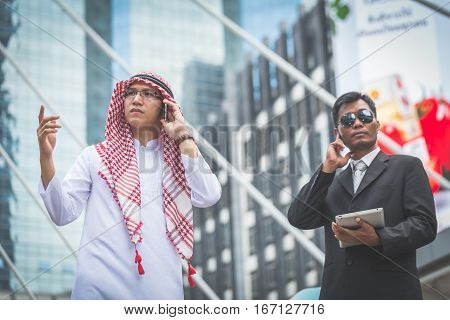 Arabic Businessman Looking Forward With His Bodyguard On Cityscape Background