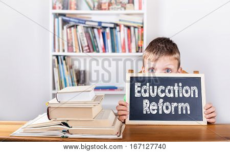 Education Reform. Boy holding chalkboard in office.