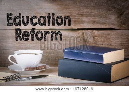Education Reform. Stack of books on wooden desk.