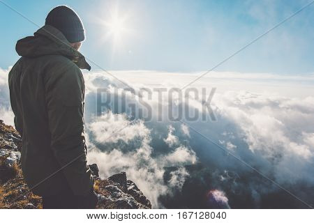 Man on mountain summit with sun over clouds Travel hiking Lifestyle success concept adventure active vacations outdoor