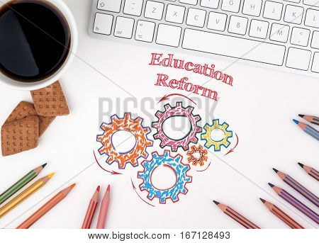 Education Reform. Computer keyboard and a coffee mug on a white table.