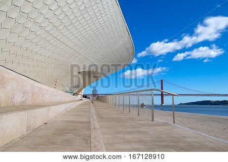 Facade of the new art technologies and architecture museum in Lisbon. The 25 April bridge over the tagus river