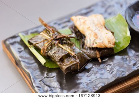 Fried chicken wrapped with pandan leaf .