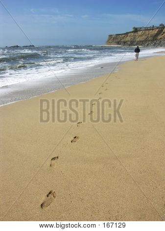 Person Walking On The Beach With Footprints