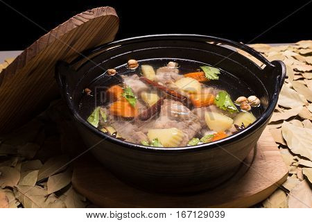 Clear oxtail soup on leaf background black background