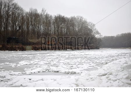 The frozen river in the winter. The snow covers the ice. The river is completely frozen