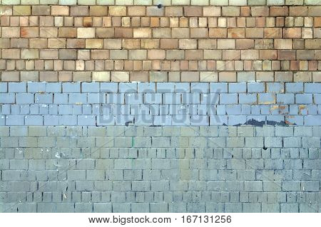 Old brick wall painted in yellow and blue texture.