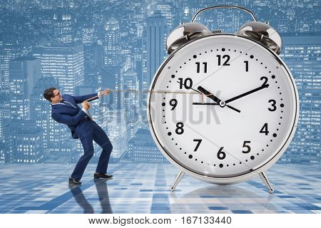 Businessman pulling clock in time management concept