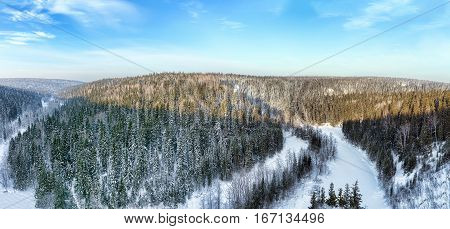 Panoramic views of the snow-covered forest in the mountains and the valley of the river