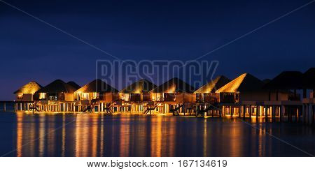 Water Bungalows Houses At Sunset, Tropical Landscape. Maldives Islands