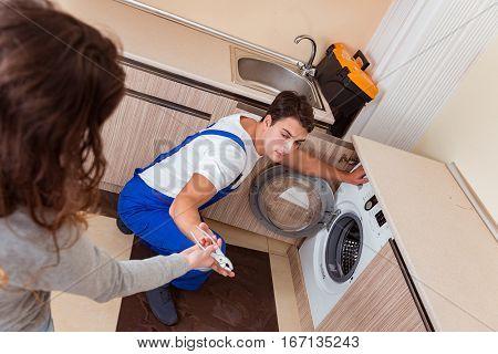 Repairman repairing washing machine at kitchen