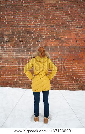 Girl in a yellow jacket looking at a brick wall