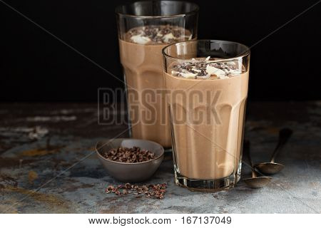 Chocolate banana smoothie with cocoa nibs and coconut flakes