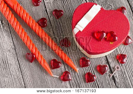 Symbols of Valentines Day. Gift box with bow, decorative red hearts, two candles and a small key on a gray wooden background. The mood of joy and love.