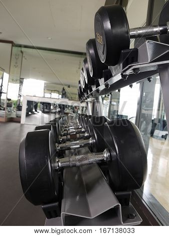 Group of black dumbbells in fitness gym