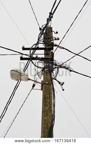 Concrete pole with electric wires on sky background