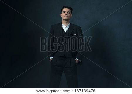 Retro 1920S English Style Gangster In Suit Against Gray Wall.