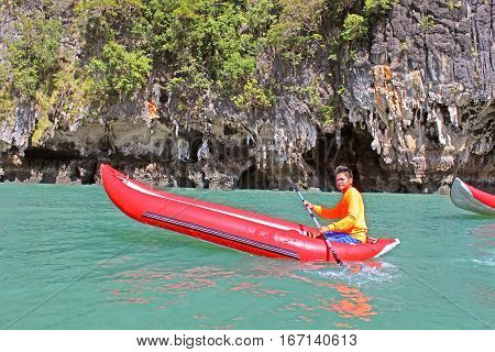 KO TAPU, THAILAND - DECEMBER 09, 2013: Man in an inflatable canoe  near Ko Tapu island in Thailand, known as James Bond Island
