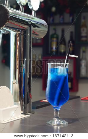 Blue cocktail in a glass on the bar.
