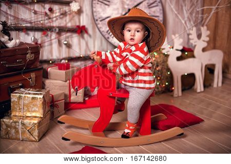 Happy Child In Big Hat On A Rocking Deer