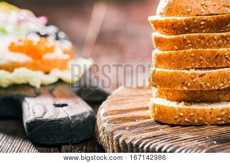 Bran bread for toasts with farmer cheese and various tops served on board