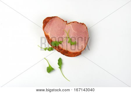 stack of sliced smoked pork meat with arugula leaves on white background