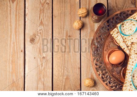 Passover concept with matzah seder plate and wine on wooden background. View from above