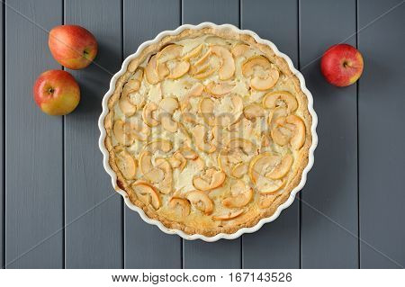 Apple tart with whole apples on grey stripped background overhead view