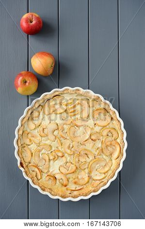 Apple tart with whole apples on grey stripped background vertical
