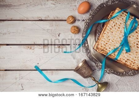Jewish holiday Passover concept with matzah seder plate and wine glass on white table background. View from above. Flat lay
