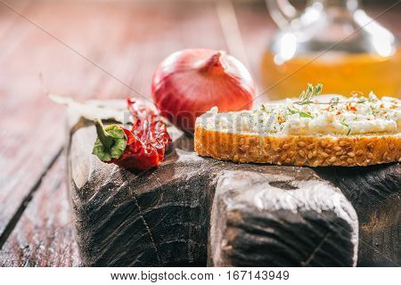 Toast with fresh farmer cheese and condiments on rustic wood board