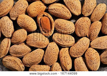 Almonds on wooden background Almond nut in shell and shelled close up