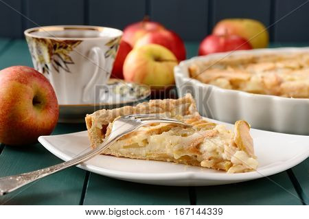 Apple tart with cup of tea and whole apples closeup