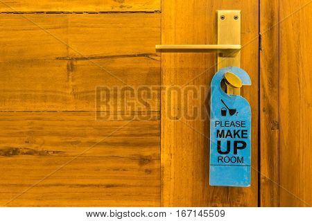 Close-up of please make up room sign on door knob in hotel