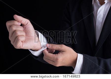 A business man in black suit is dressing up, fastening closing shirt sleeve buttons.