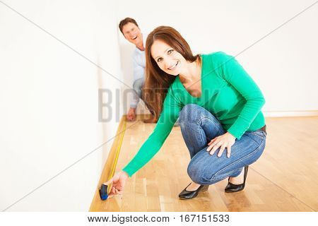 adult couple measuring the rooms in their new apartment