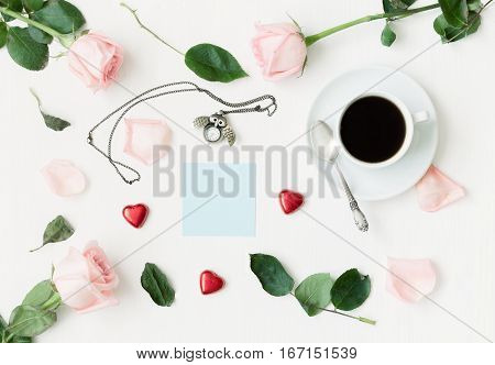 St Valentines day still life - cup of coffee peach roses blue sheet of note owl shaped clock heart shaped candies on white background. St Valentines day still life