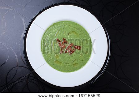 Green cream soup with sun dried tomatoes