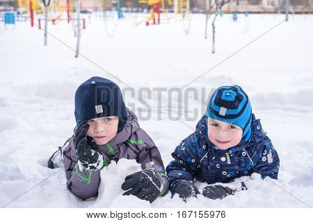 Two Boys Sitting In The Snow Covered Landscape On The Playground. Winter Trees With And Ice, Mountai