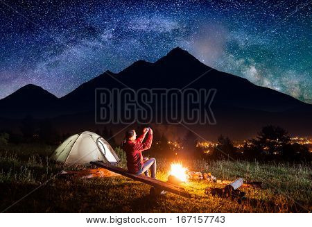 Female Sitting Near Tent And Makes Photo Of Starry Sky