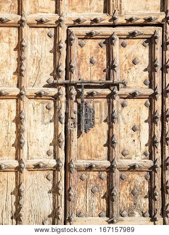 ancient brown wooden door with metallic ornaments and a big bolt