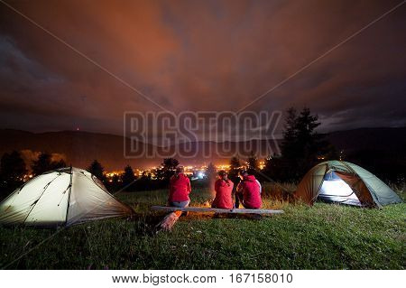 Friends Sitting On Bench And Watching Fire Together Beside Camping