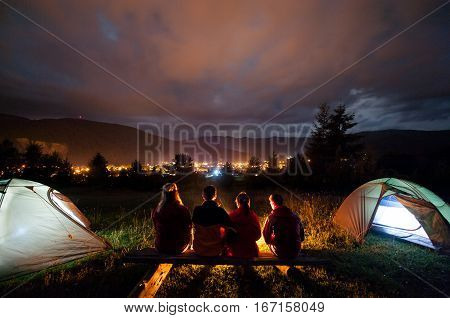 Silhouette Of Four People Watching Fire Together In The Camping