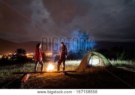 Evening Camping. Man And Woman Standing By The Campfire
