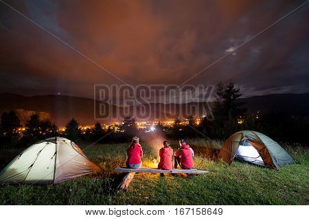 People Watching Fire Together Beside Camp And Tents In Dark