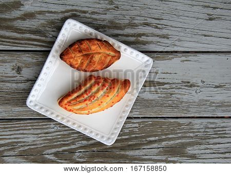 Gray wood background with simple white dish and two fancy pastries