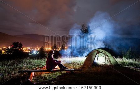 Thoughtful Woman Sitting On A Bench Near Tent And Campfire