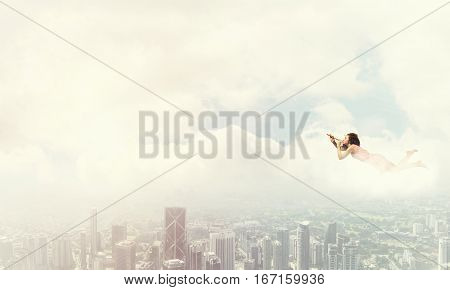 Young pretty woman flying in sky and playing fife
