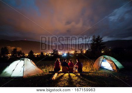 Friends Sitting Beside Camp And Tents In The Evening