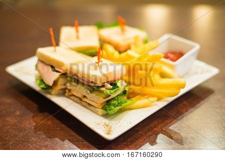 Mini sandwiches with fried fries and sauce on a white plate